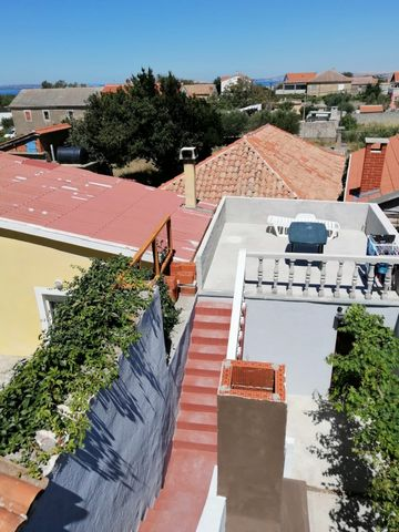 Location: Zadarska županija, Vrsi, Vrsi. We are selling a house in Vrsi of 105 m2 with a yard, roof terraces and sea views. The house has two bathrooms, two bedrooms, kitchen and living room. The plots have enough for comfortable socializing in pants...